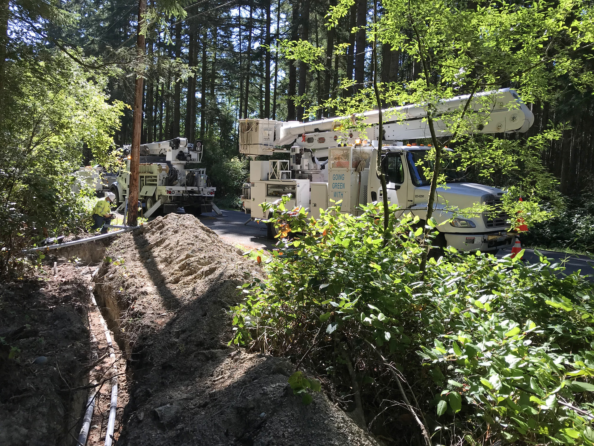 Utilities ditch with conduit by Parker Road with Puget Sound Energy PSE trucks