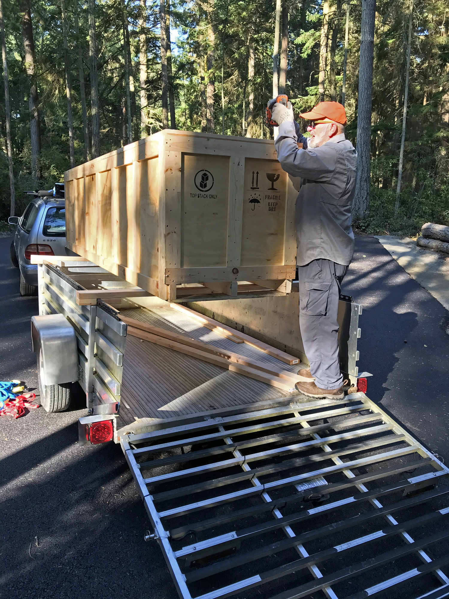 Ken Price opening crate for Jeff Kahn Wind Shear at Price Sculpture Forest sculpture park Coupeville Whidbey Island
