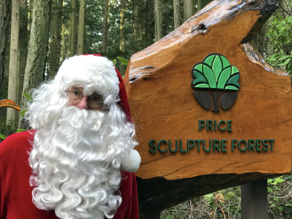 Santa Claus at entrance sign to Price Sculpture Forest park garden in Coupeville on Whidbey Island