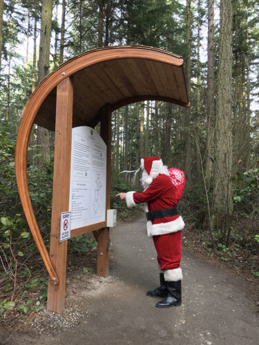 Santa Claus reading entry kiosk at Price Sculpture Forest park garden in Coupeville on Whidbey Island