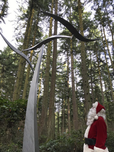 Santa Claus viewing Jeff Kahn's Wind Shear at Price Sculpture Forest park garden in Coupeville on Whidbey Island