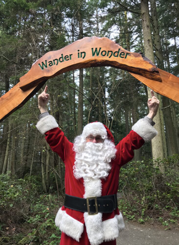 Santa Claus pointing to Wander in Wonder entry arch to Price Sculpture Forest park garden in Coupeville on Whidbey Island