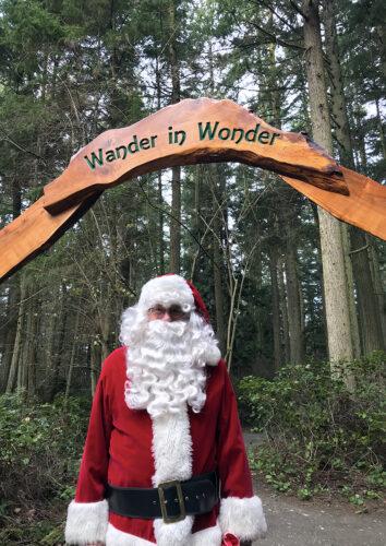 Santa Claus under Wander in Wonder entry arch to Price Sculpture Forest park garden in Coupeville on Whidbey Island