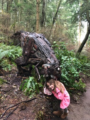 Caela Easton with Joe Treat Tyrannosaurus Rex at Price Sculpture Forest - by Maggie Easton of Oak Harbor WA