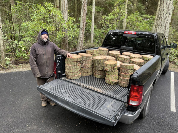 Artist Anthony May with cut log rounds in his truck at Price Sculpture Forest