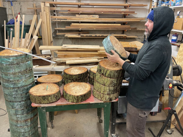 Artist Anthony May inspecting arrangement of cut log rounds for Price Sculpture Forest installation