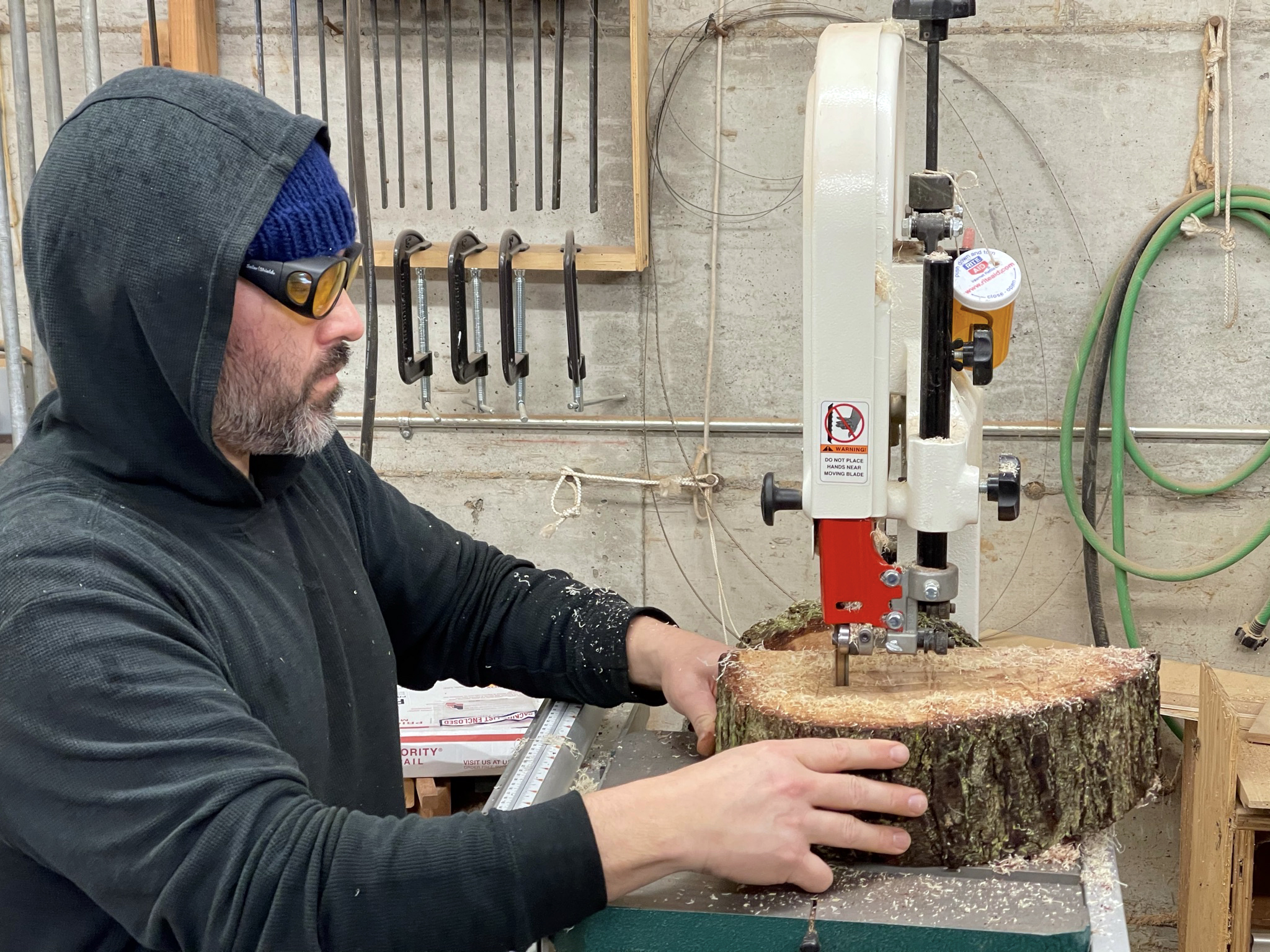 Artist Anthony May using bandsaw to cut log rounds into smaller pieces for Price Sculpture Forest installation