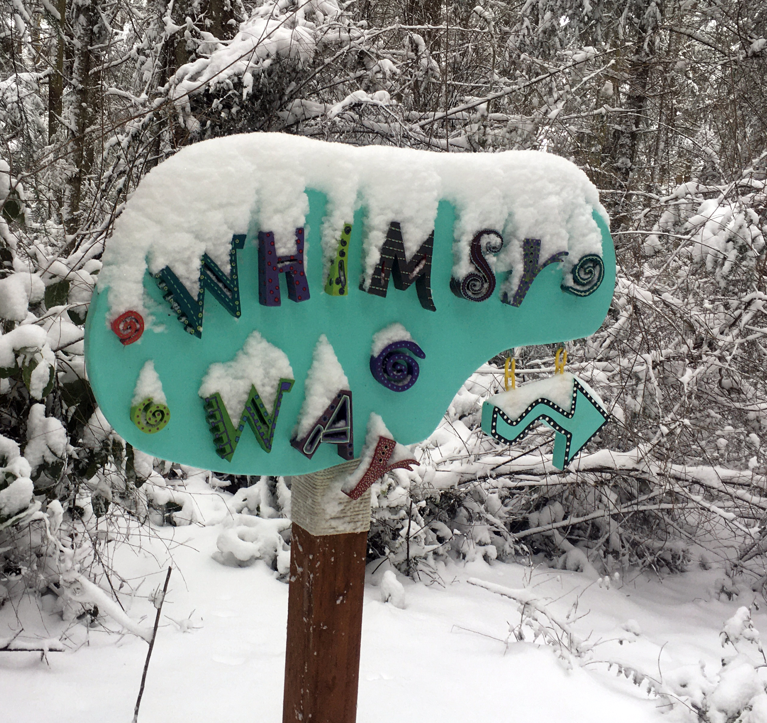 Whimsy Way trail sign by Linda Hauser covered in snow at Price Sculpture Forest park garden Coupeville Whidbey Island