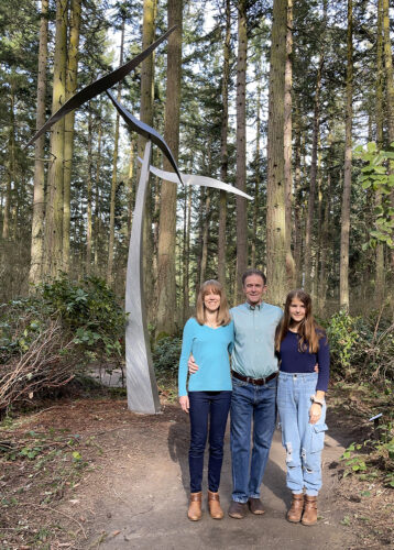Karen, Scott, and Lydia Price at Price Sculpture Forest in front of Wind Shear by Jeff Kahn
