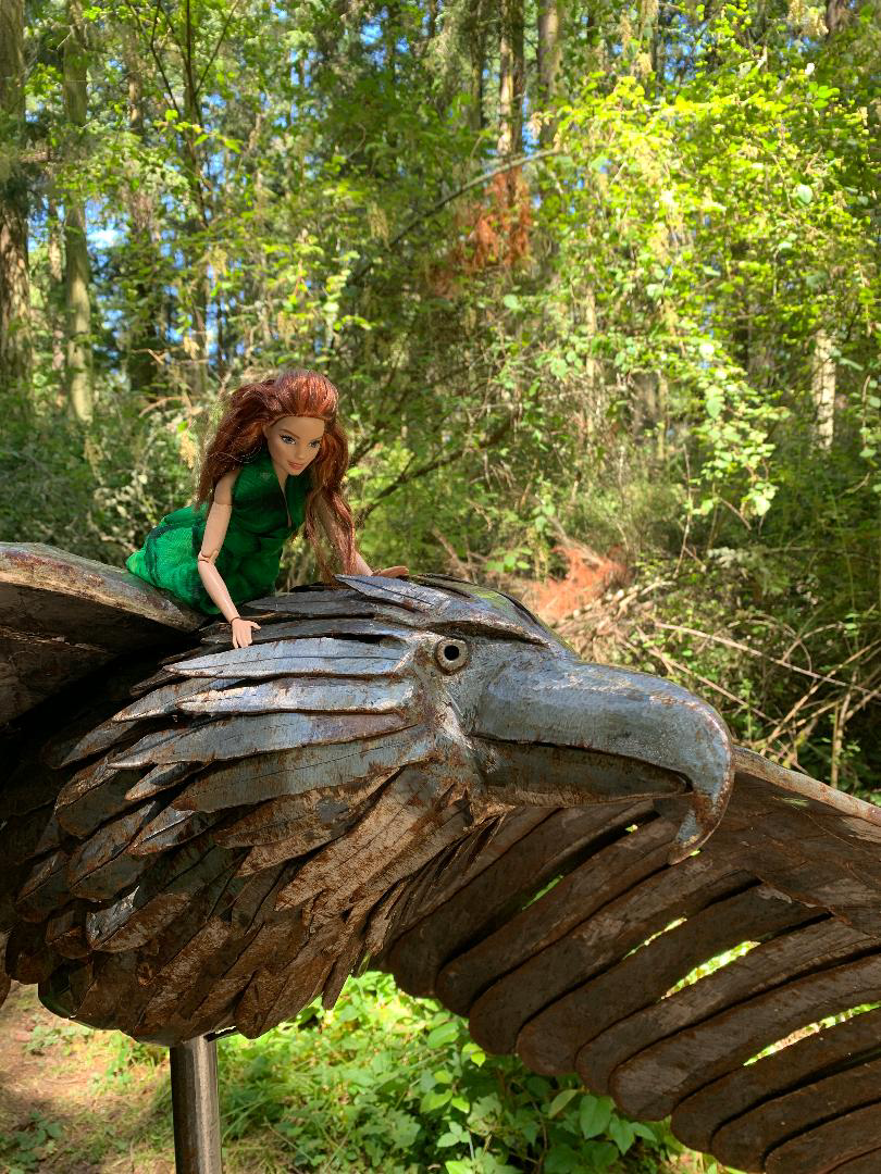 Feminist Barbie flies on Soaring Eagle by Greg Neal at Price Sculpture Forest park garden in Coupeville on Whidbey Island - photo by Liz Jackson
